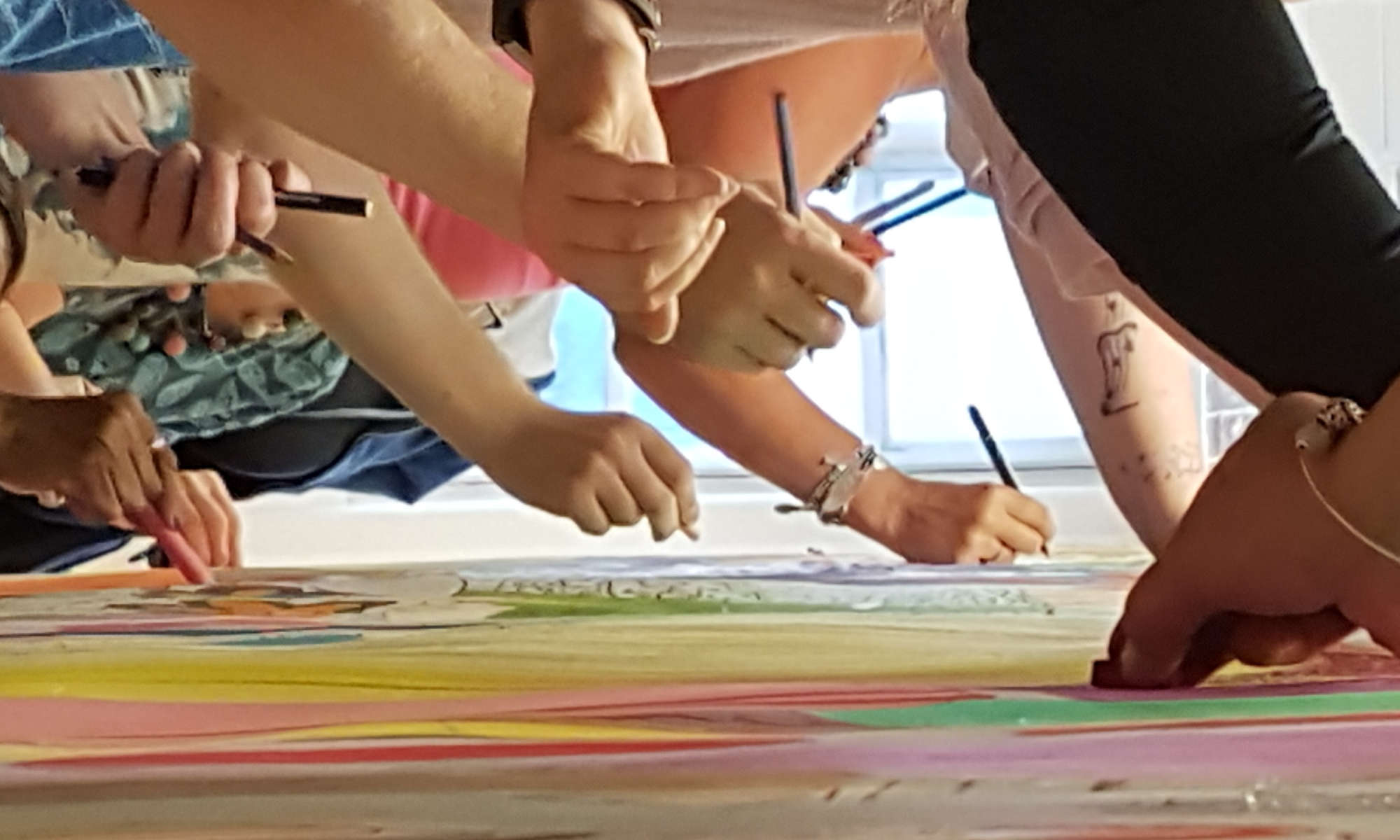 Image of many hands cocreating a collaborative 8gate art piece